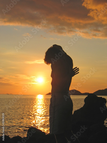 a man with strange forms in the sunset, labuan bajo, pede beach,