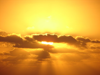 yellow golden sun glowing through clouds