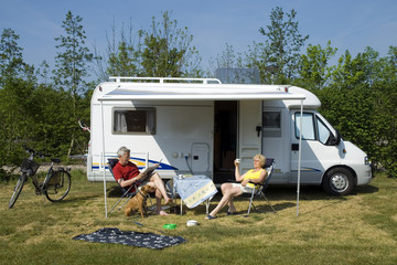 an elderly couple with camper