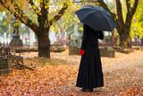 Žena ve smutku na hřbitově na podzim