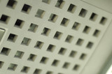 square holes in white plastic plate poster