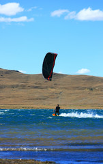 black and red kitesurfer cruising