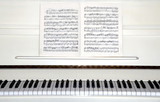 white piano with sheet music poster