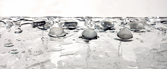 glass pebble stone on wet water surface with drops