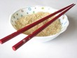 bowl full of uncooked rice grains with chopsticks