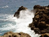waves over lava rocks poster