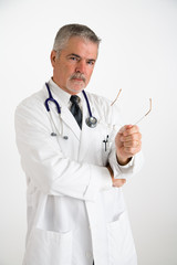 doctor holding eyeglasses explaining