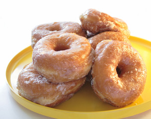 fresh glazed doughnuts on a yellow plate