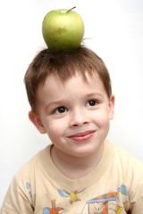the cheerful child with a green apple on a head