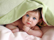 beautiful baby looking out from under blanket - 3283602