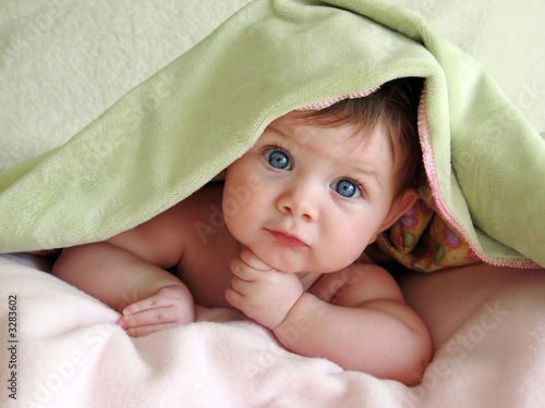 beautiful baby looking out from under blanket