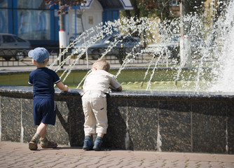 two boys at a fountain