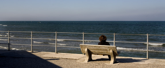 lonely woman sitting on a bench on the seafront