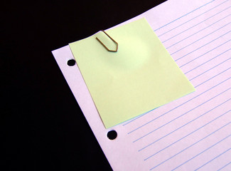 clipped yellow paper on lined paper background