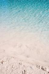 blue water ripples on white sandy beach