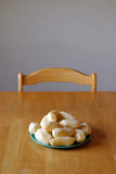 peeled potatoes sitting on dinner table poster