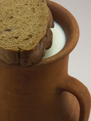 jug with milk and bread on white