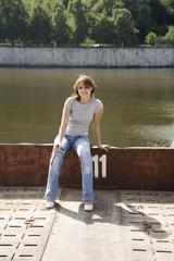 pretty girl sitting on the riverbank