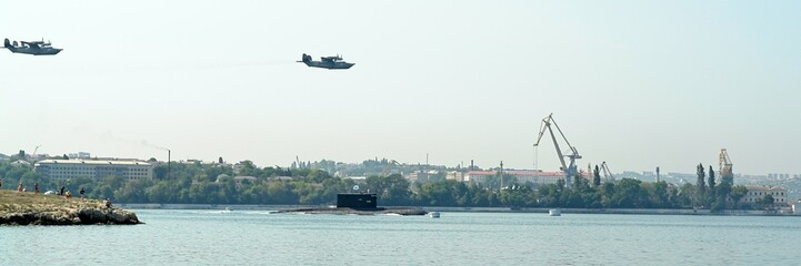 military planes fly by above a submarine