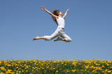 Fototapety girl flying in a jump over dandelion field