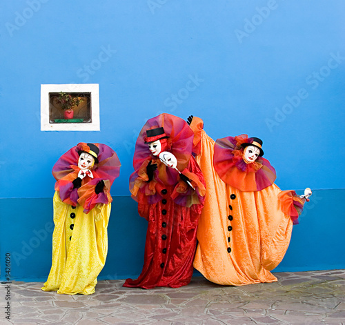 three white clowns in mask performing