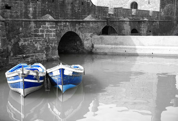 black and white harbour with two blue boats