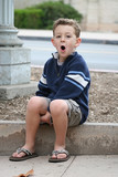 Little Boy sitting on curb