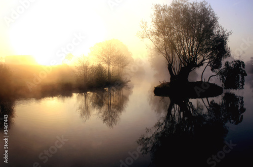 dramatic sunrise over a misty lake at dawn
