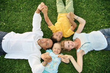 family lying on a grass