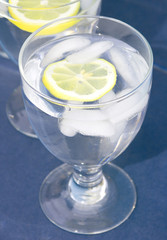 chilled glass of water with lemon slice on blue ba