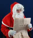 Santa studying the stocks and shares in the newspaper