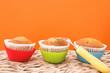 three vanilla muffins in plastic cups
