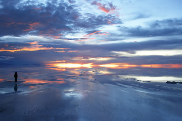 person watching sunset over wet salt flats