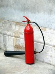 extincteur rouge contre mur de pierre