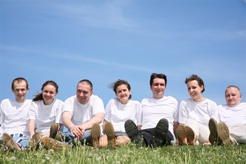 Group of friends in white T-shorts have a rest on a grass