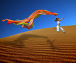 rainbow woman jumping over the dunes
