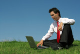 young man using laptop outdoors poster