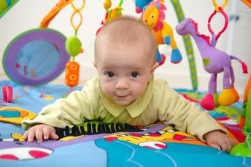 bébé en train de jouer sur un tapis d eveil
