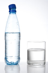 bottle and glass with water and reflection on white