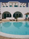 beautiful swimming pool by the beach in kamari poster