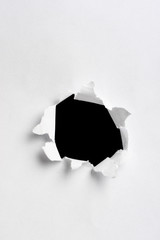 black hole in white paper with ragged edges