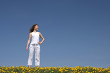 Calm young woman standing in a flowering spring field. poster