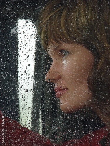 Girl looks thru waterdropped widow glass in rainy weather