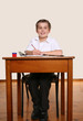 Happy smiling young school boy sitting at school desk/