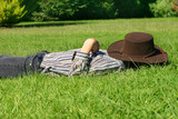 A child lays in grassy field taking a rest or siesta. poster