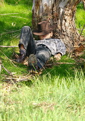 Child sleeps under  gum tree in a secluded spot of the range