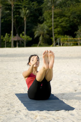 A young attractive asian woman working out doing yoga on beach