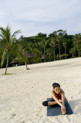 A young asian woman working out on the tropical beach