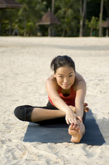A young woman performs a yoga stretch on a tropical beach