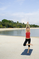 A young woman practising yoga on the beach